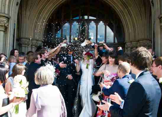 Happy wedding day with guests throwing confetti